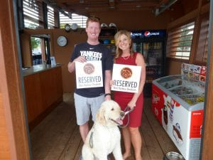 couple holding up reserved signs with west harbour logo on them while also holding a dog on a leash