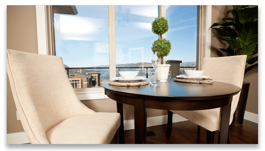 two tan chairs sat with table and houseplant with window overlooking west harbour