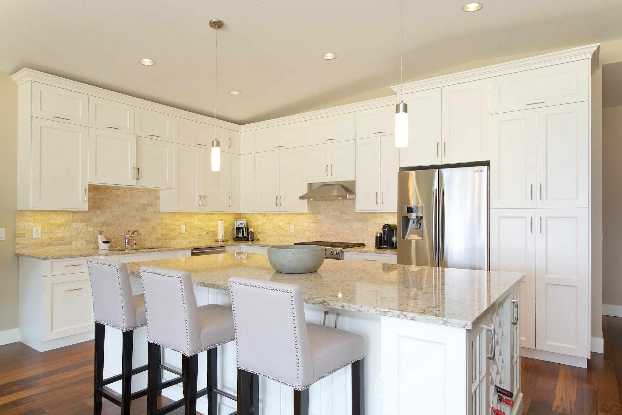interior shot of west harbour home kitchen with white cabinetry bar chairs fridge and stove