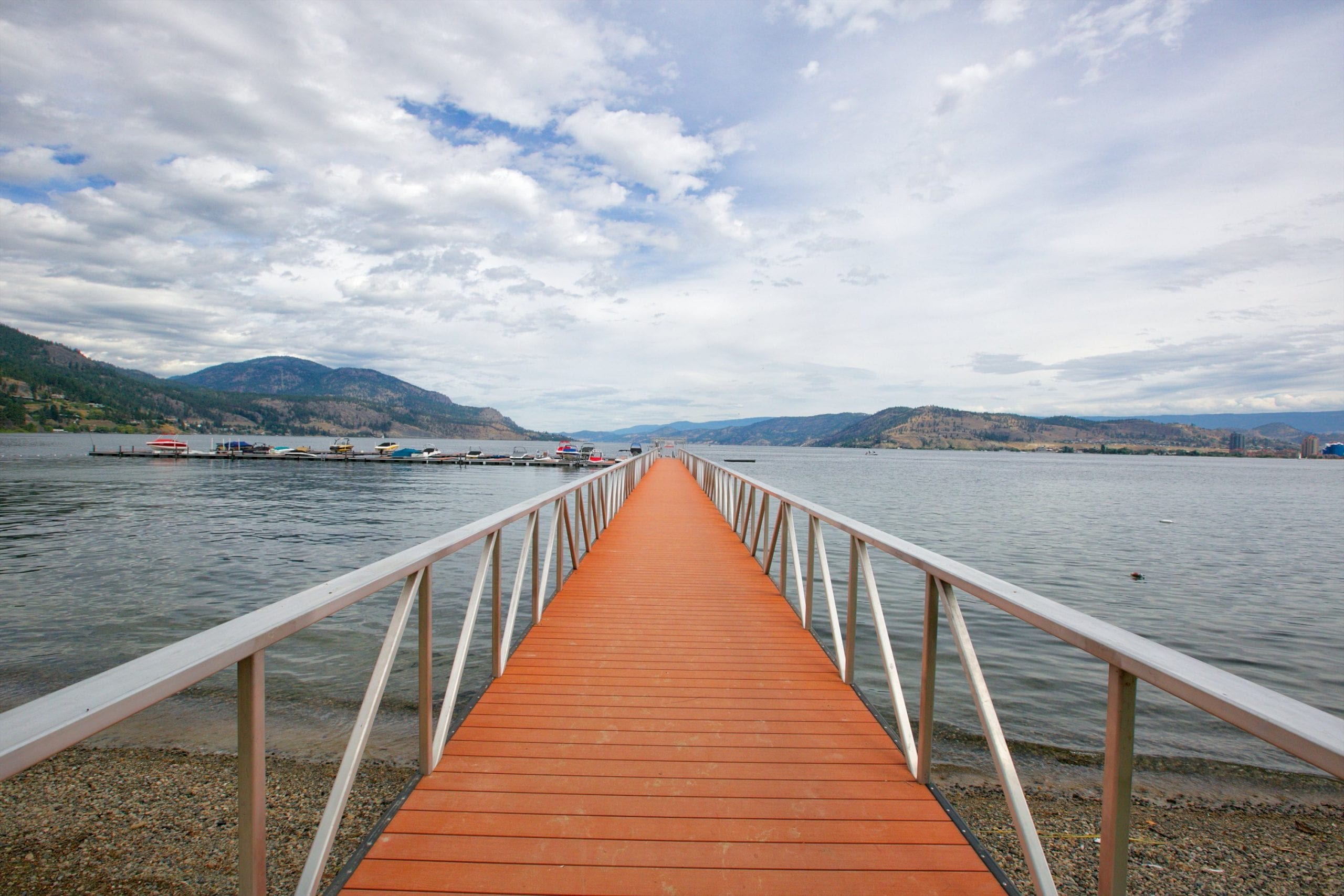 walkway shot staring directly at the marina on the okanagan lake with multiple boats parked