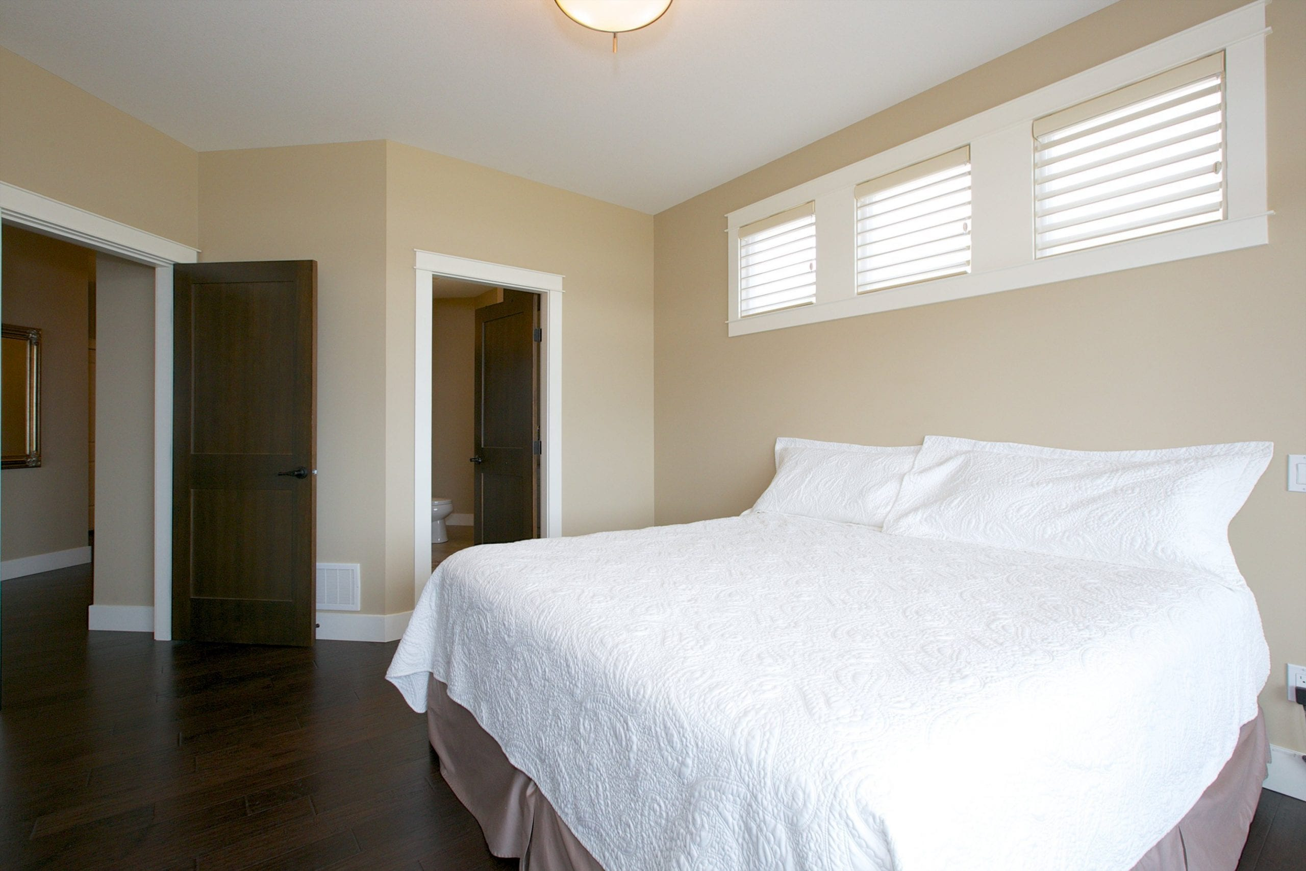 interior shot of west harbour home master bedroom with three windows directly above the bed and two doors in view