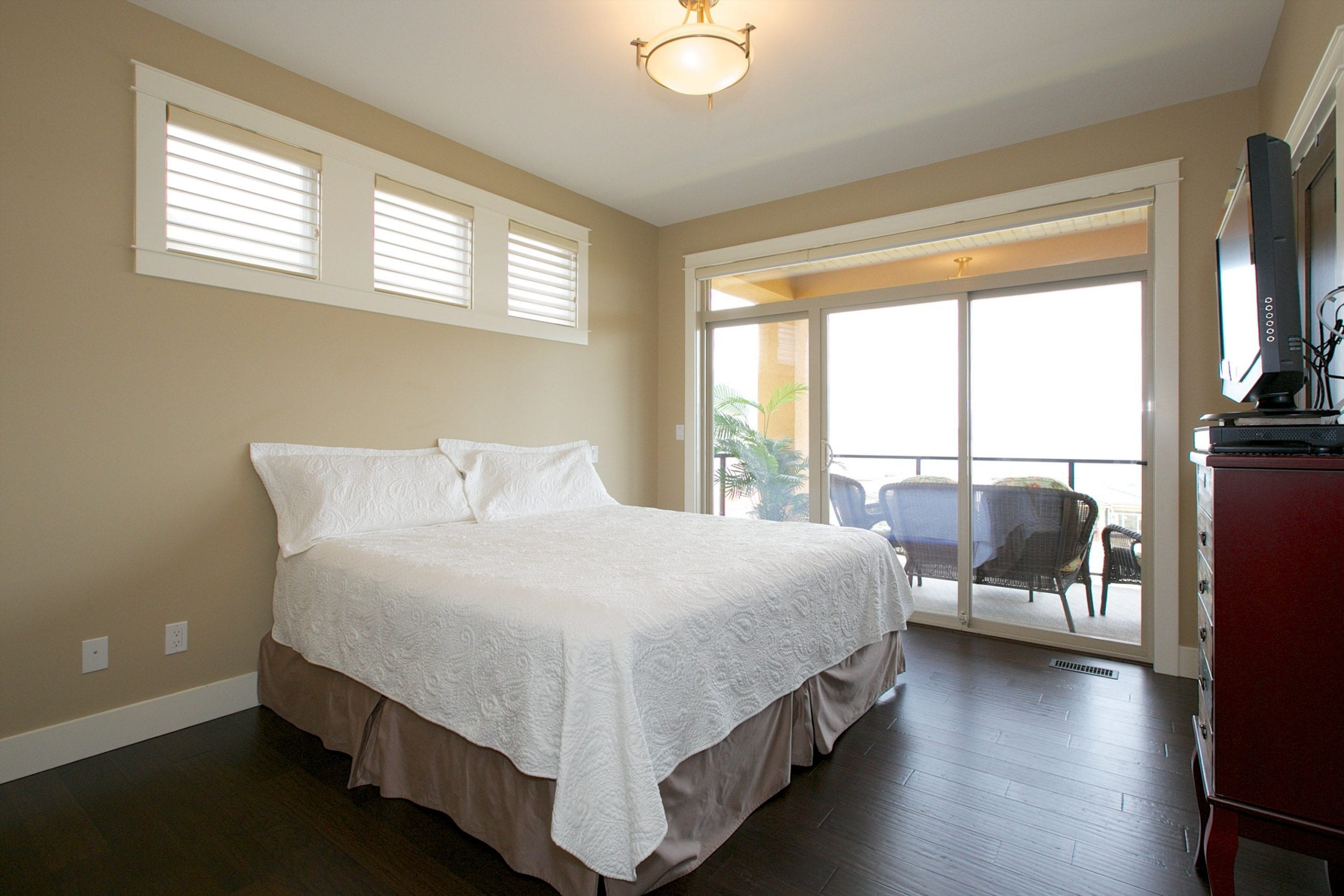 interior shot of west harbour home master bedroom with bed facing a television and four windows bringing in natural light