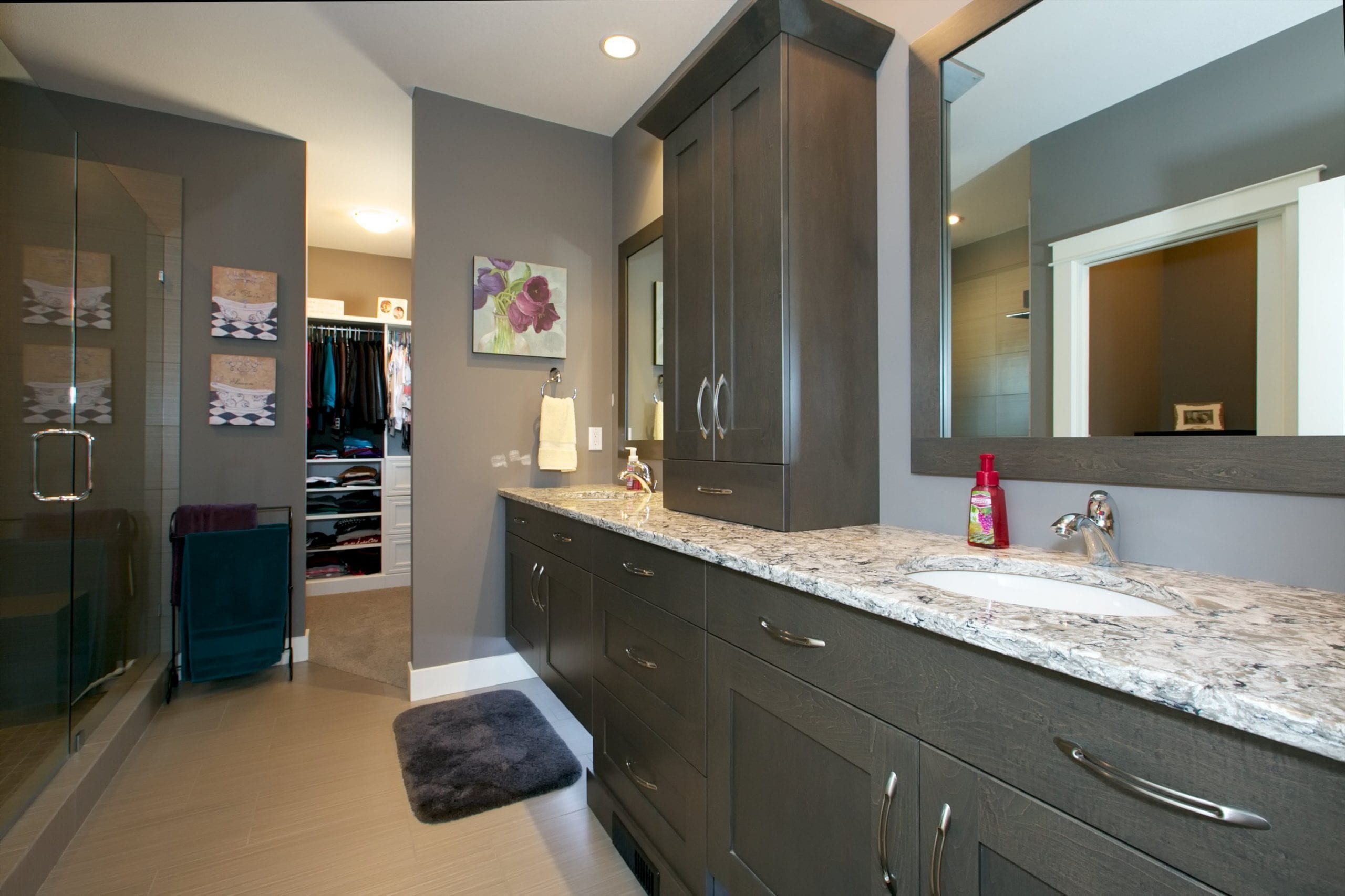 interior shot of westharbour home master bathroom with a his and hers sink assorted cabinetry and a walk in closet