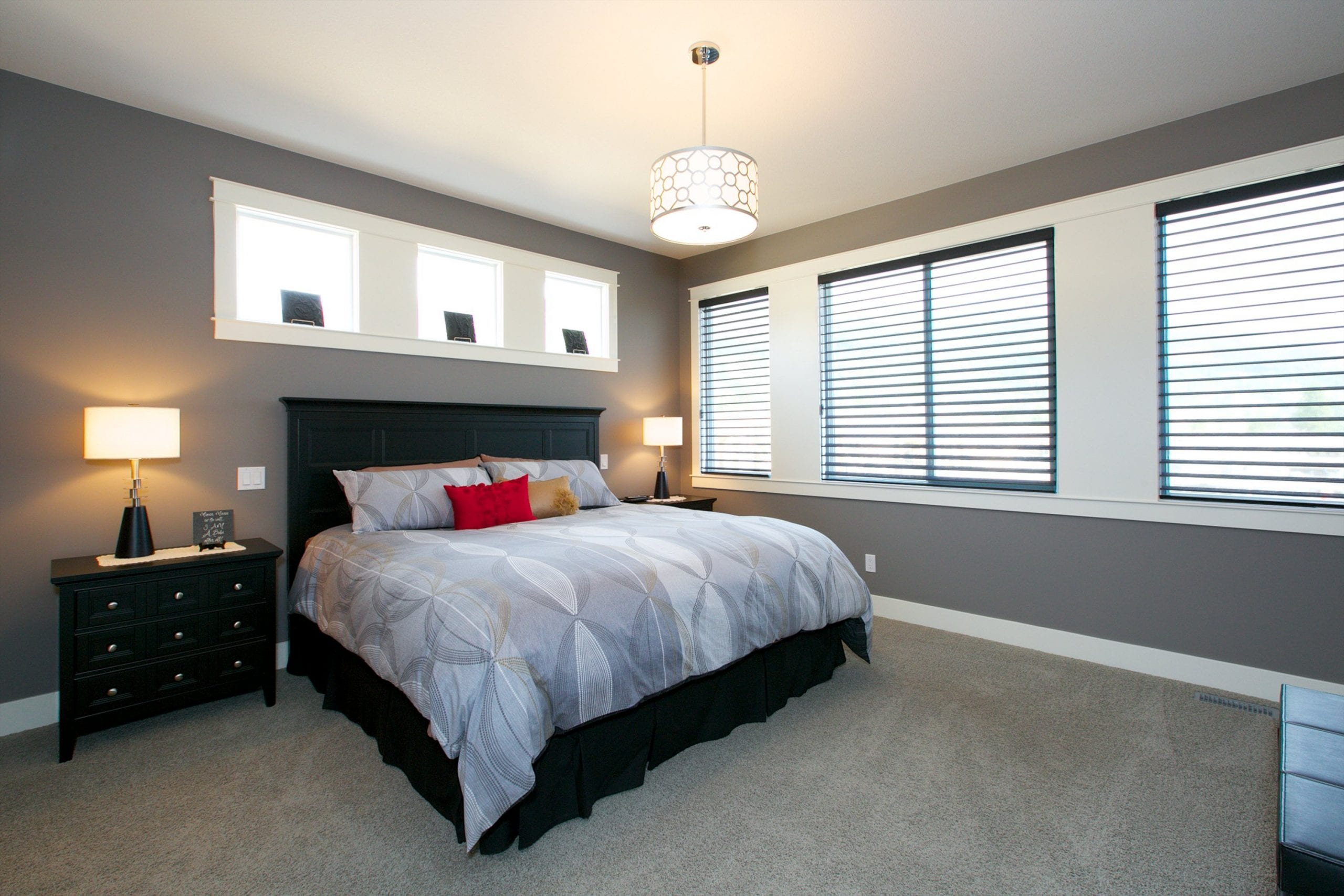 interior shot of west harbour home master bedroom with three windows above the bed flanked by two nightstands