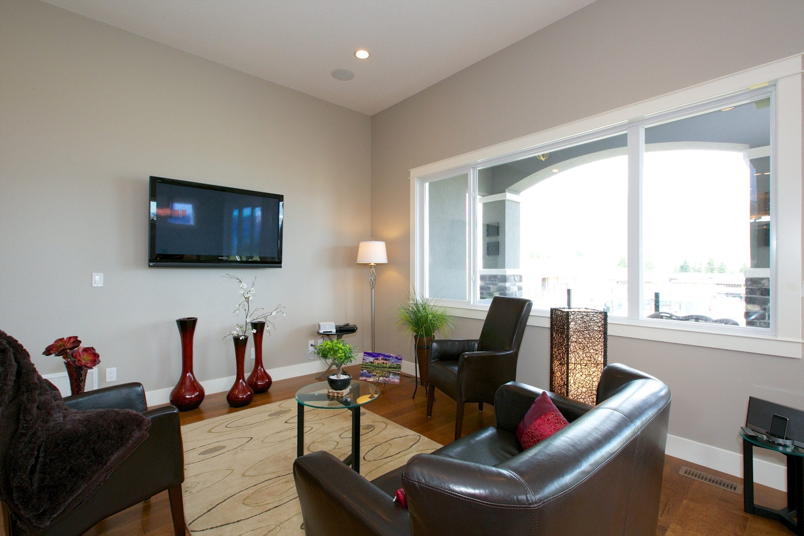 interior shot of west harbour home family room with small mounted television a couch and two chairs and a large window