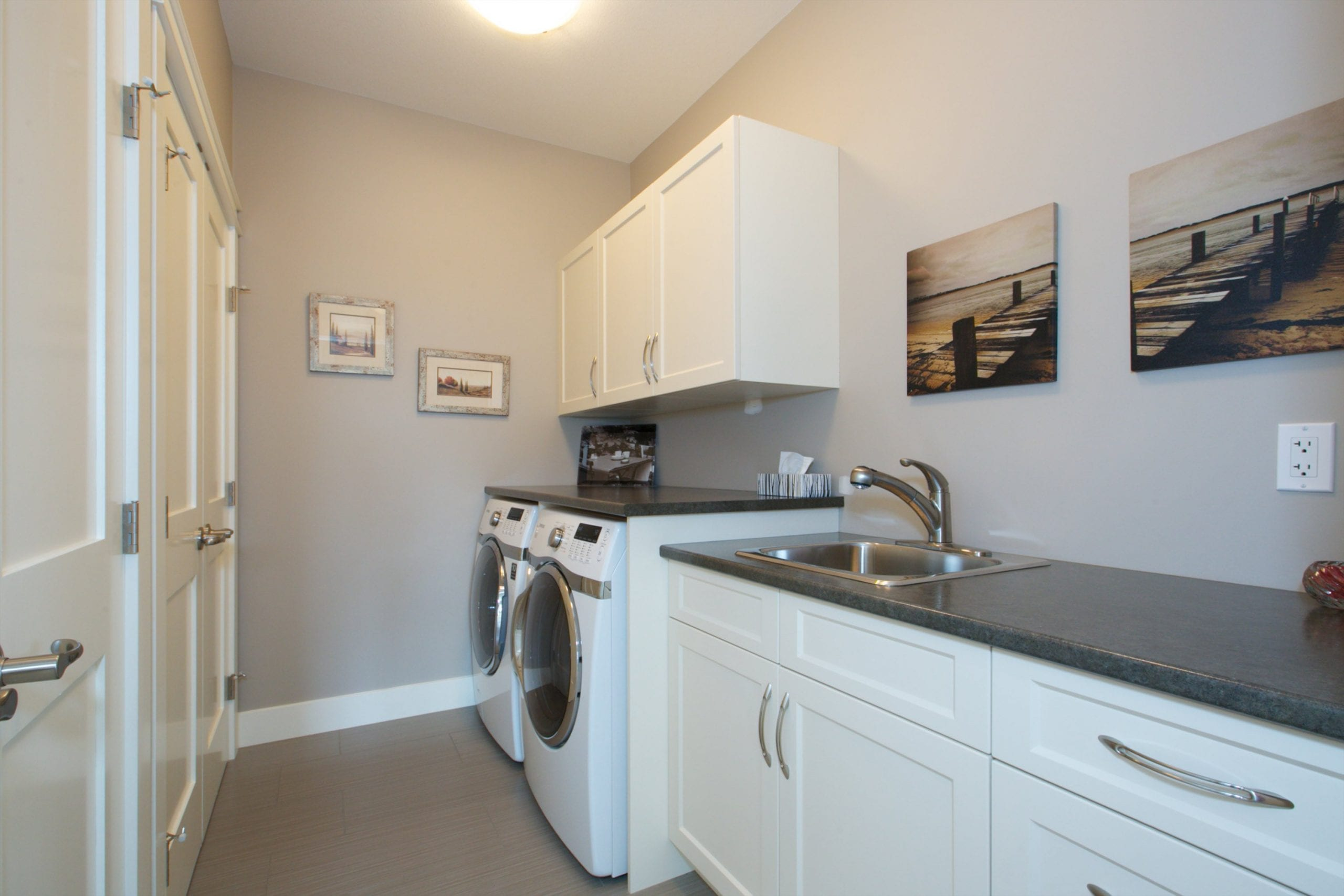 interior shot of west harbour home laundry featuring a sink with cabinetry both below and above a washer and a dryer