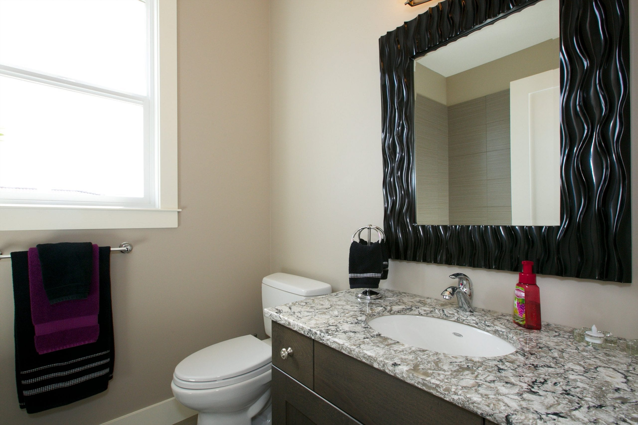 interior shot of west harbour home bathroom featuring a toilet a mirror a sink and multiple towels hung up