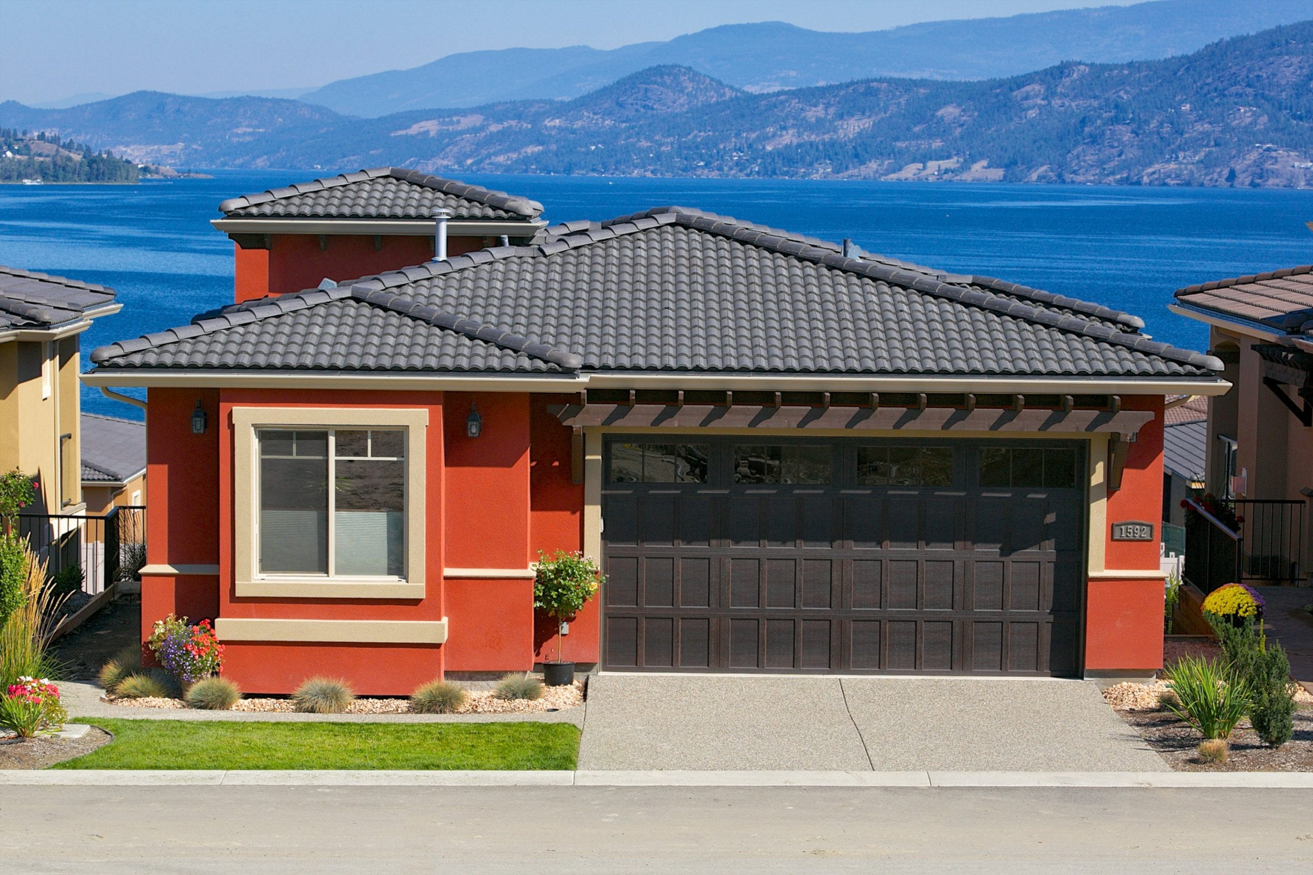 exterior shot of red chianti home with tan details in west harbour overlooking the lake in the background