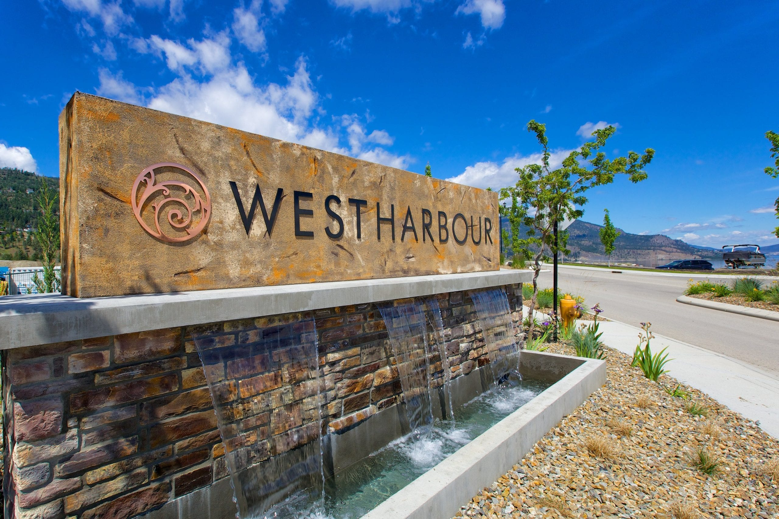 west harbour sign with little fountain streaming from it and okanagan lake in background