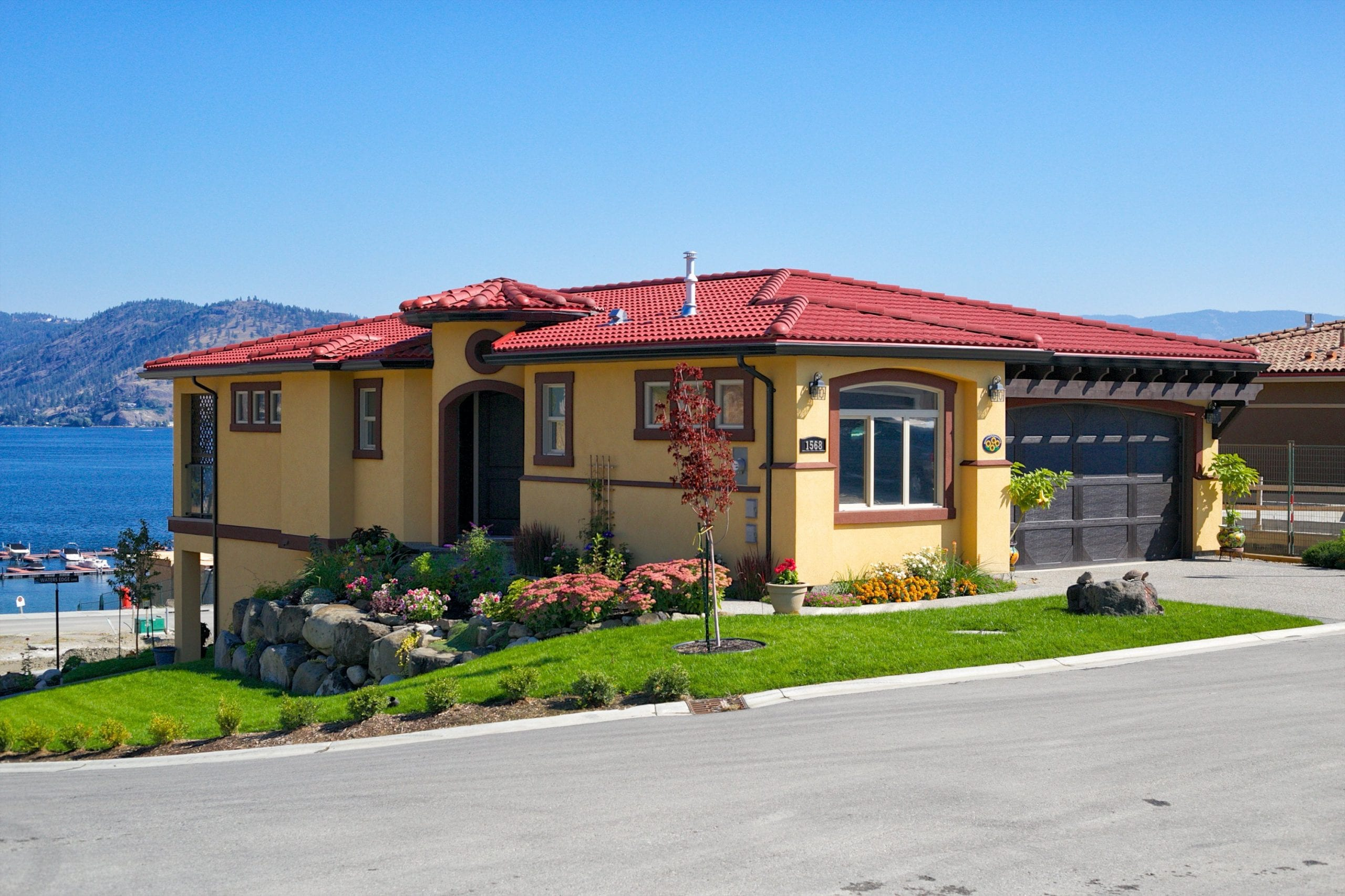 exterior shot of chardonnay roofed home with parmesan main body overlooking okanagan lake on a clear day