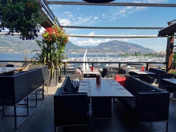 Earls rooftop kelowna nice chairs and tables with houseplant overlooking the docks okanagan lake and the mountains